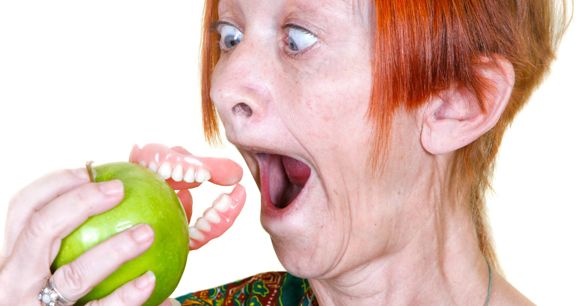 implant-dentist-photo features woman whose false teeth dentures fell out while eating an apple.